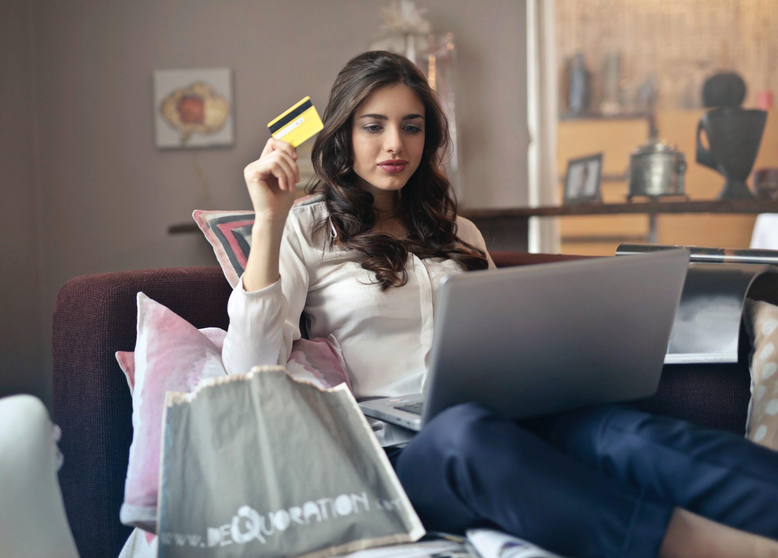 kobieta przed komputerem z kartą kredytową